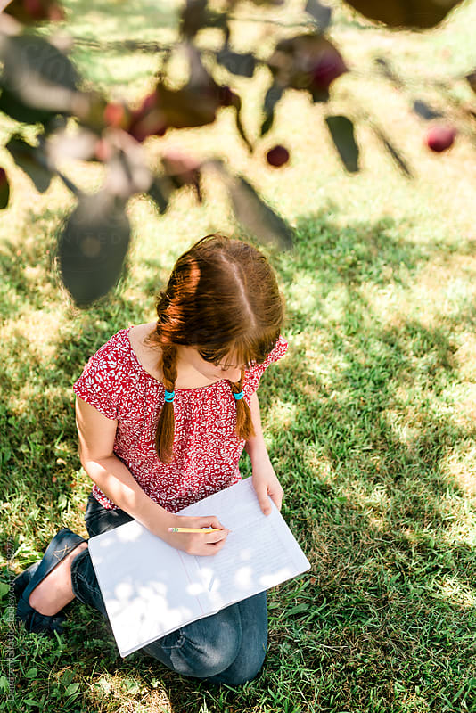 redhead journaling in the shade by Deirdre Malfatto for Stocksy United