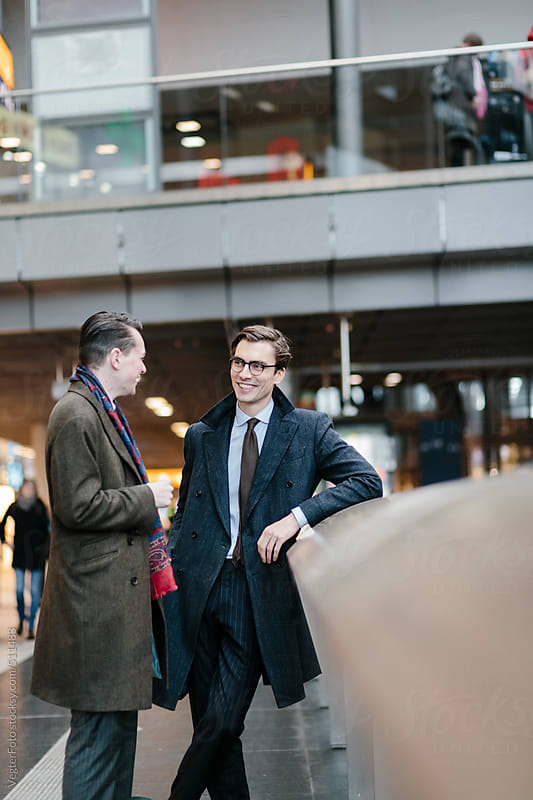 Two Businessman Chatting On Train Station by VegterFoto for Stocksy United