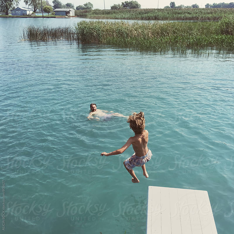 A Boy Jumping Off A Diving Board Into A Blue Lake While His Dad Watches From The Water by ALICIA BOCK for Stocksy United