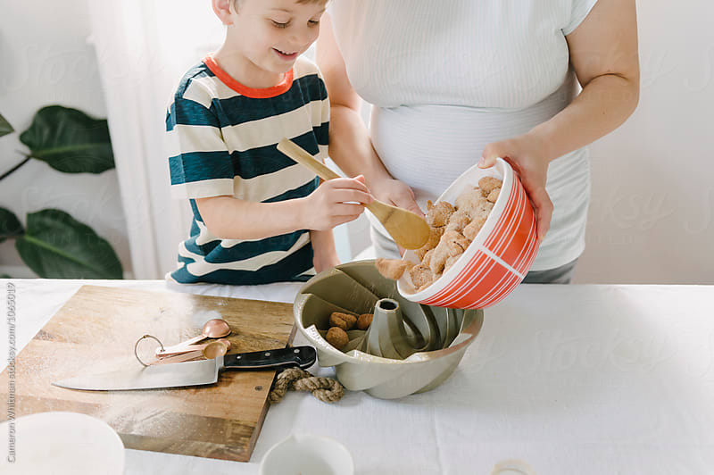 Mother and Son working together making Monkeybread by Cameron Whitman for Stocksy United