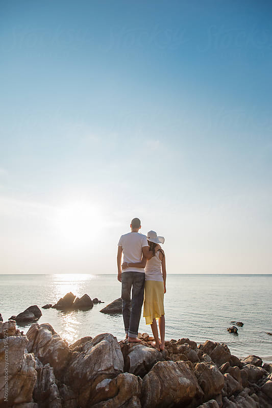 Couple Standing on the Rocks and Enjoying Sunset by Mosuno for Stocksy United