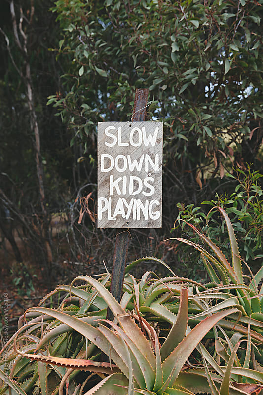 Hand painted sign - Slow down kids playing by Natalie JEFFCOTT for Stocksy United