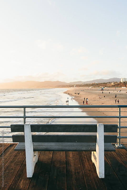 Bench looking towards beach on top of a pier by Alejandro Moreno de Carlos for Stocksy United
