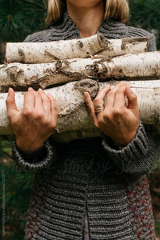 Woman in forest holding firewood by Gabriel (Gabi) Bucataru for Stocksy United