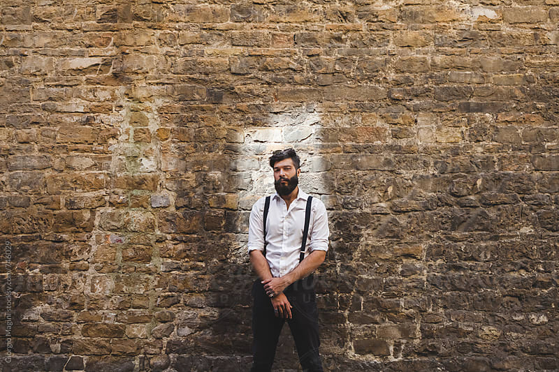 Tough Italian Young Man Standing in front of a Stone Wall by Giorgio Magini for Stocksy United