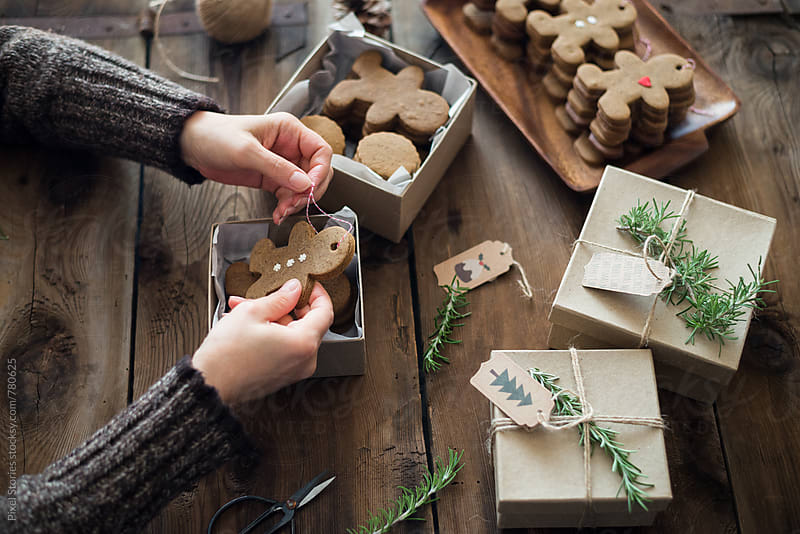 Gift-wrapping Gingerbread men cookies by Pixel Stories for Stocksy United