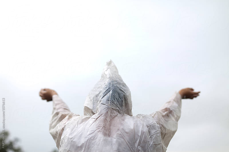 Teenage girl making stretching hand wearing rain coat,Rear View by PARTHA PAL for Stocksy United