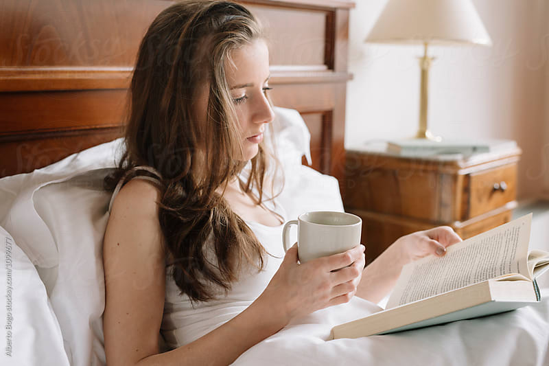 Beautiful girl reading book with cup of coffee by Alberto Bogo for Stocksy United
