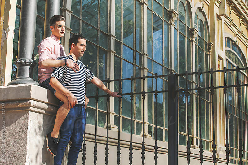 Young gay couple standing in front a greenhouse.  by BONNINSTUDIO for Stocksy United