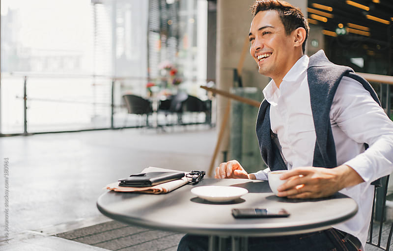 Smiling businessman working from a coffeeshop by Jovo Jovanovic for Stocksy United