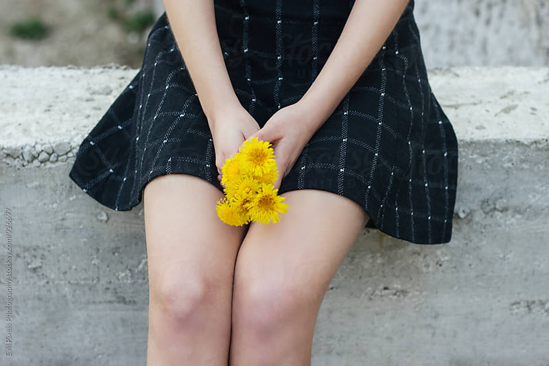 Close up of anonymous female model holding dandelions by Branislava Živić for Stocksy United