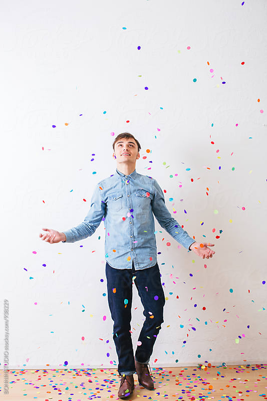 Young man playing as confetti falls from above. by BONNINSTUDIO for Stocksy United