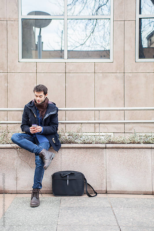 Modern guy typing messages on phone. by Audrey Shtecinjo for Stocksy United