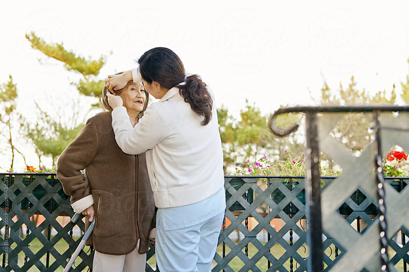 Homecare Nurse Connecting with Elderly Patient by Joselito Briones for Stocksy United