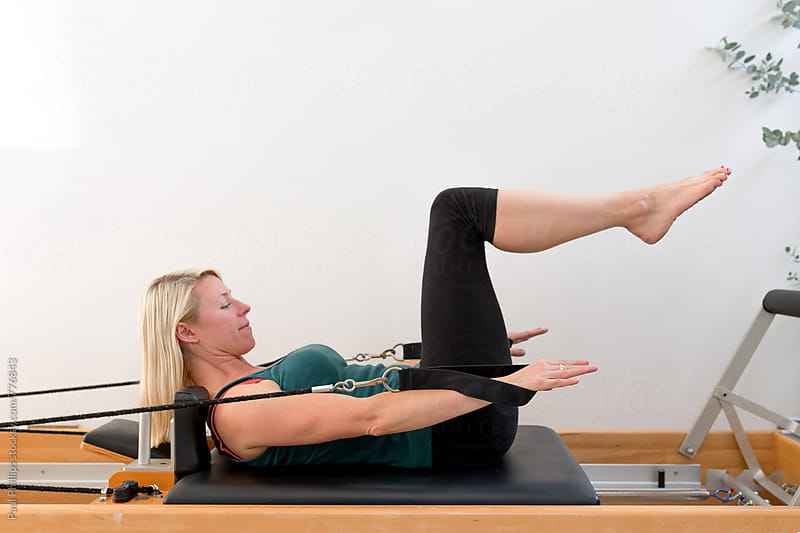 Pilates exercise the hundred undertaken on the Reformer. Woman (30s) by Paul Phillips for Stocksy United