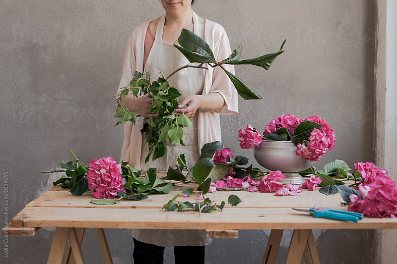 woman in her workshop preparing some orchid flower by Lydia Cazorla for Stocksy United