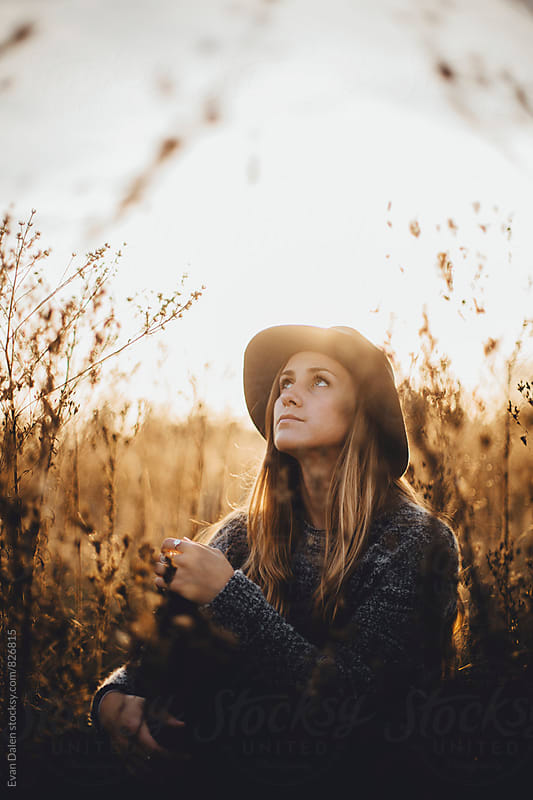 Young Woman Sitting In Field Looking At Sky by Evan Dalen for Stocksy United