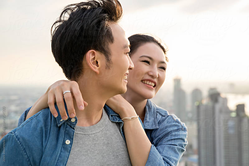 Portrait of a happy Asian couple laughing  by Jovo Jovanovic for Stocksy United