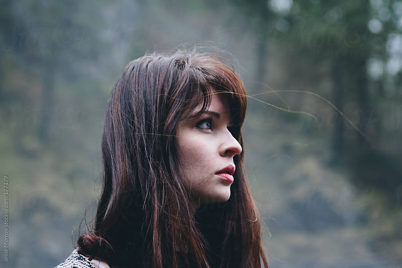 Young woman looks into the distance by Jesse Morrow for Stocksy United