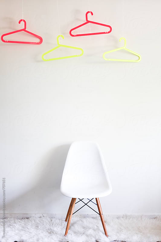 white chair and neon hangers by Treasures & Travels for Stocksy United