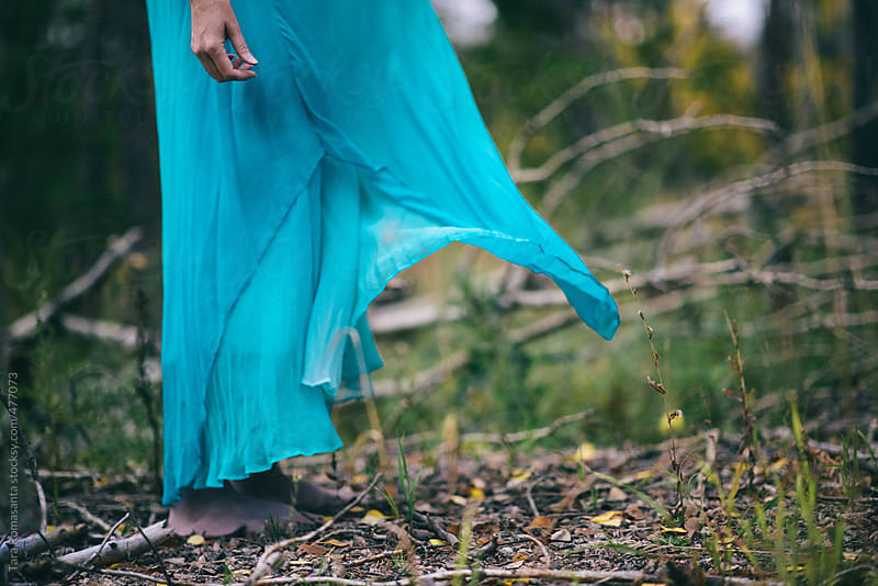 anonymous woman in billowy blue dress stands barefoot outside by Tara Romasanta for Stocksy United