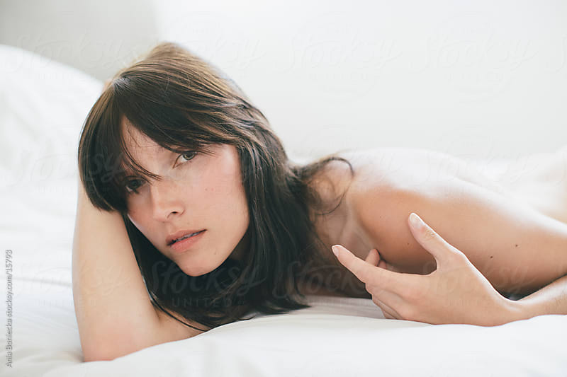 A topless woman lying in bed by Ania Boniecka for Stocksy United