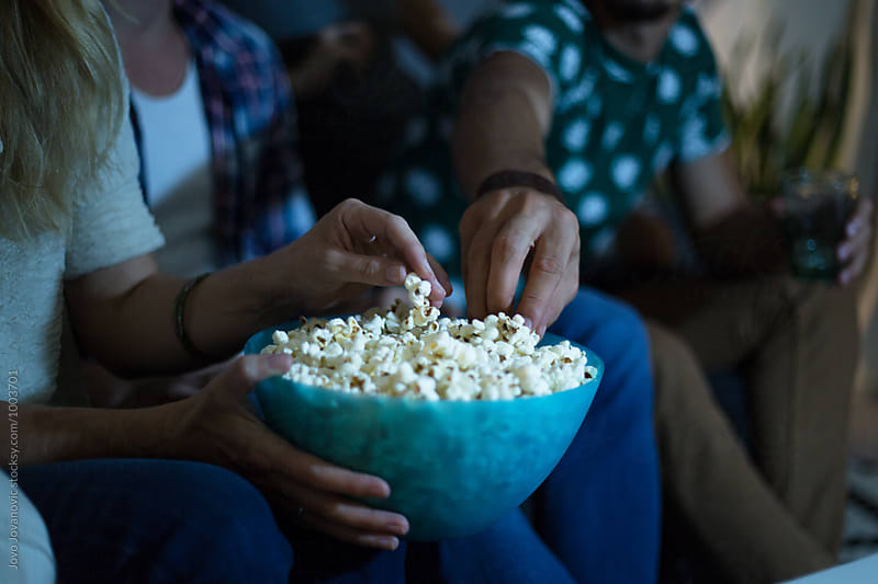 Group of friends watching tv together and eating popcorns by Jovo Jovanovic for Stocksy United