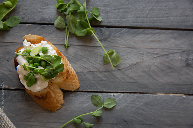 Crostini with ricotta, peas and pea shoots by Helen Rushbrook for Stocksy United