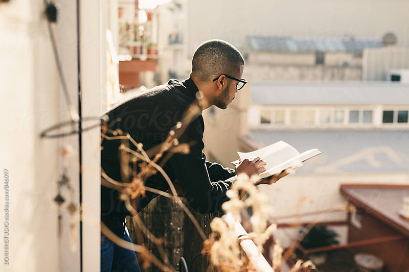 Latin man in the balcony reading a book. by BONNINSTUDIO for Stocksy United