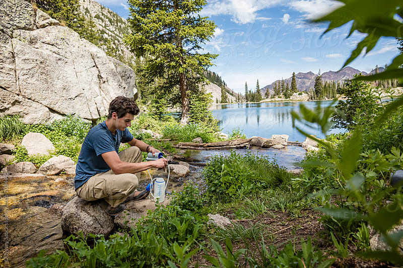 Hiker Filters Water From Stream by Odyssey Stock for Stocksy United