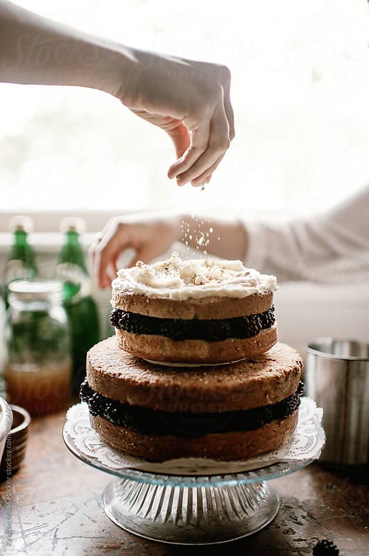 Two tierd naked layer cake is decorated by two females  by Kristen Marie Parker for Stocksy United