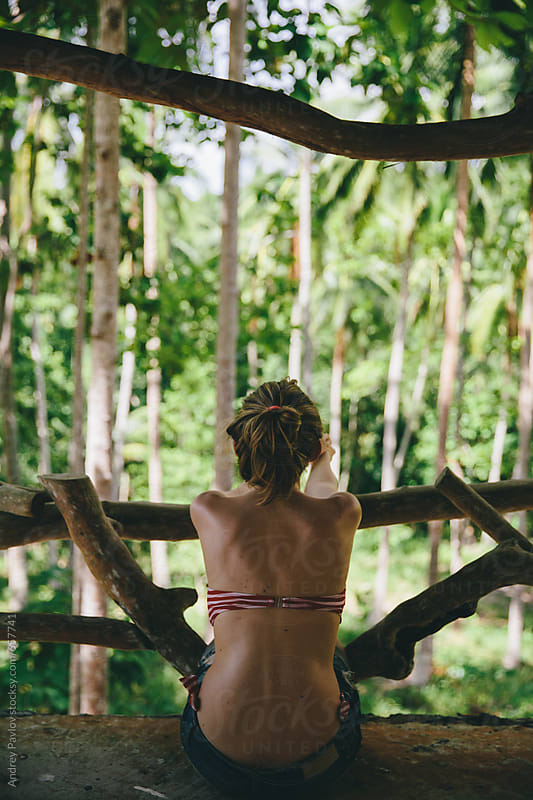 Woman on balcony looking at jungle by Andrey Pavlov for Stocksy United