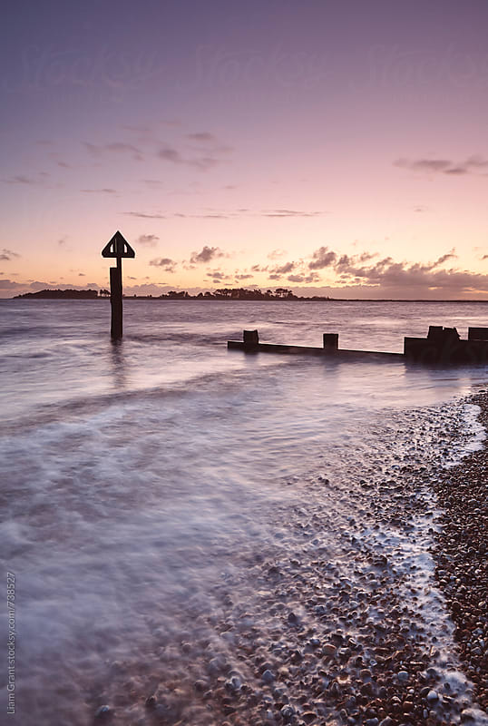 Waves breaking round a groyne at sunrise. Wells-next-the-sea, Norfolk, UK. by Liam Grant for Stocksy United