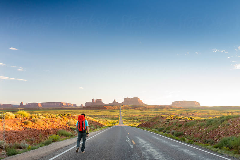 Backpacker Hiking at Mile 13 Forrest Gump Point on US 163 Leading Into Monument Valley Utah in Early Evening by JP Danko for Stocksy United