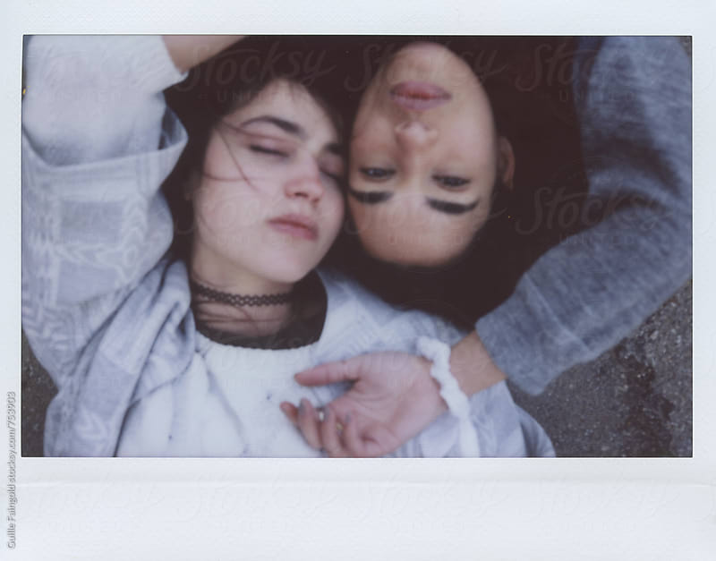two women lying on the street by Guille Faingold for Stocksy United