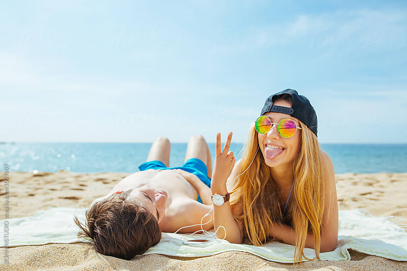 Teenage couple having fun tanning on the beach. by BONNINSTUDIO for Stocksy United