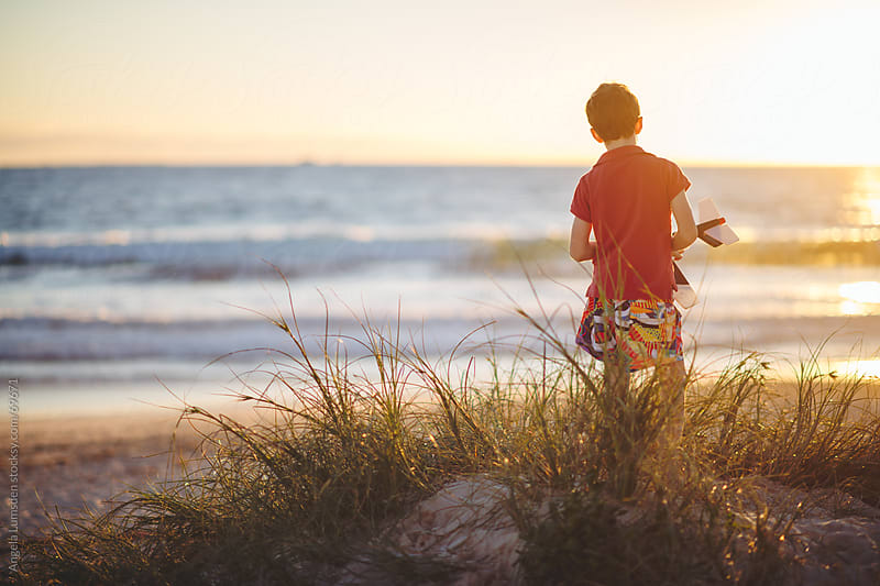 Boy standing with a toy plane at the beach by Angela Lumsden for Stocksy United