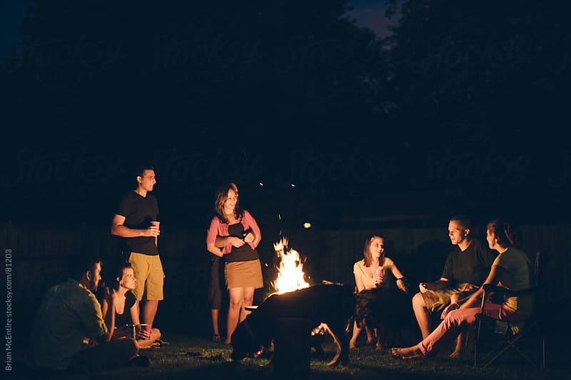 Family Pet and Friends Gathered Around a Campfire by Brian McEntire for Stocksy United
