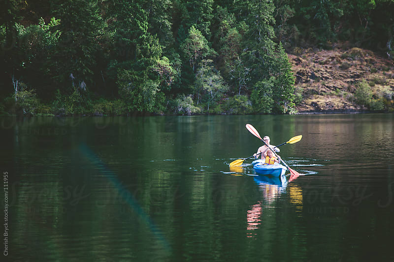 Father and daughter kayaking at the lake. by Cherish Bryck for Stocksy United