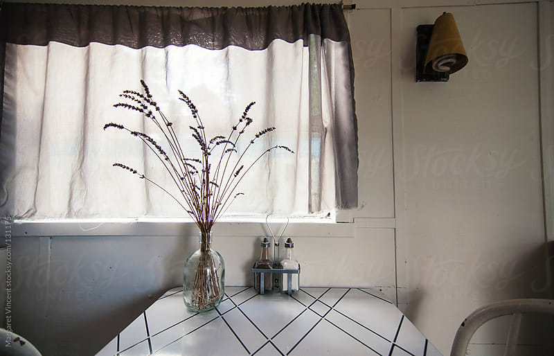 a simple kitchen table with a vase holding stems of long grass by Margaret Vincent for Stocksy United