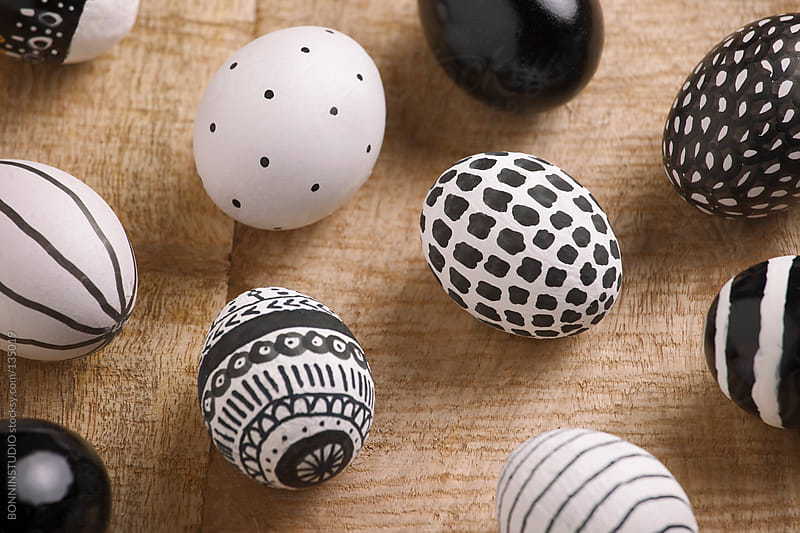 Closeup of Easter eggs with different drawings on a wood background. by BONNINSTUDIO for Stocksy United