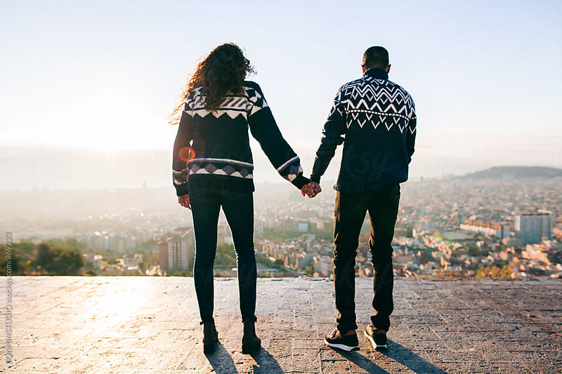 Back view of couple holding hands above Barcelona. by BONNINSTUDIO for Stocksy United