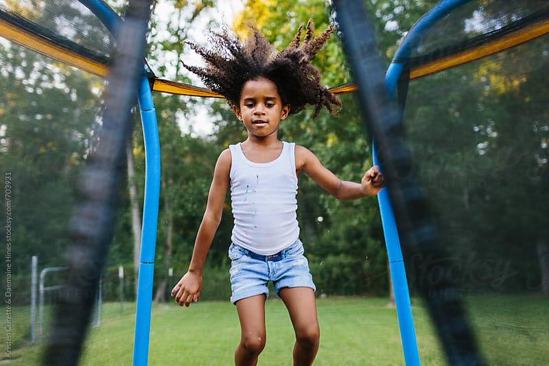 A child having fun on a trampoline outdoors  by Kristen Curette Hines for Stocksy United