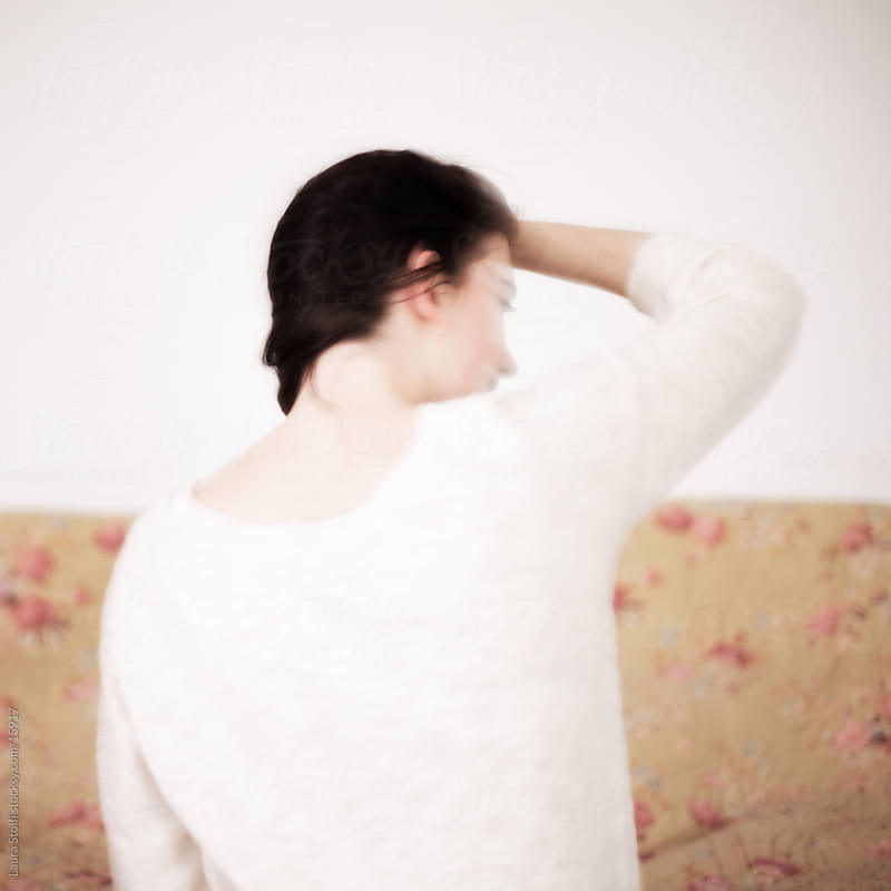 Rear sight of girl sitting on the bed with her face blurred by Laura Stolfi for Stocksy United