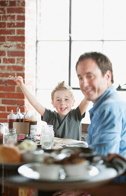 Barbeque: Child Cheers as Server Brings Food by Sean Locke for Stocksy United
