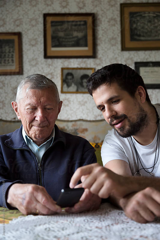 Adult grandson explaining to his granddad how to use a smartphone by Jovana Milanko for Stocksy United