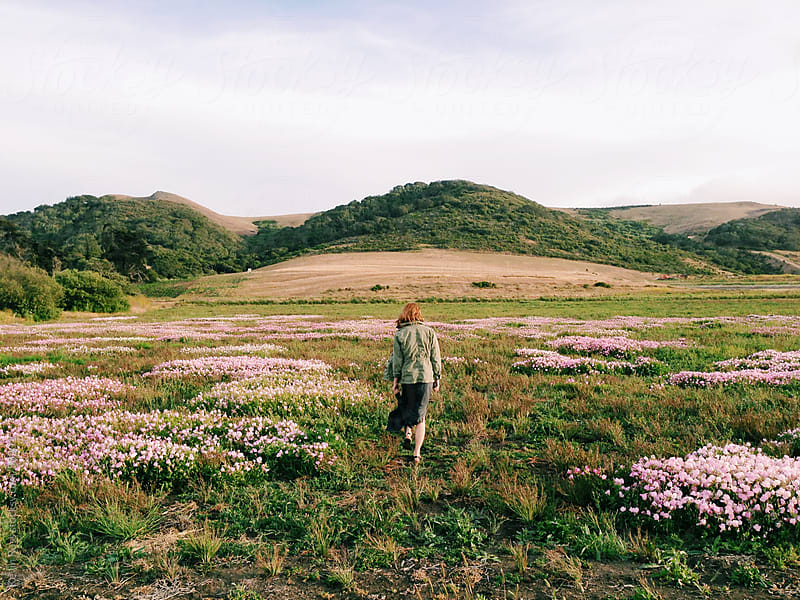 Woman Walking Through Wildflowers by Kevin Russ for Stocksy United