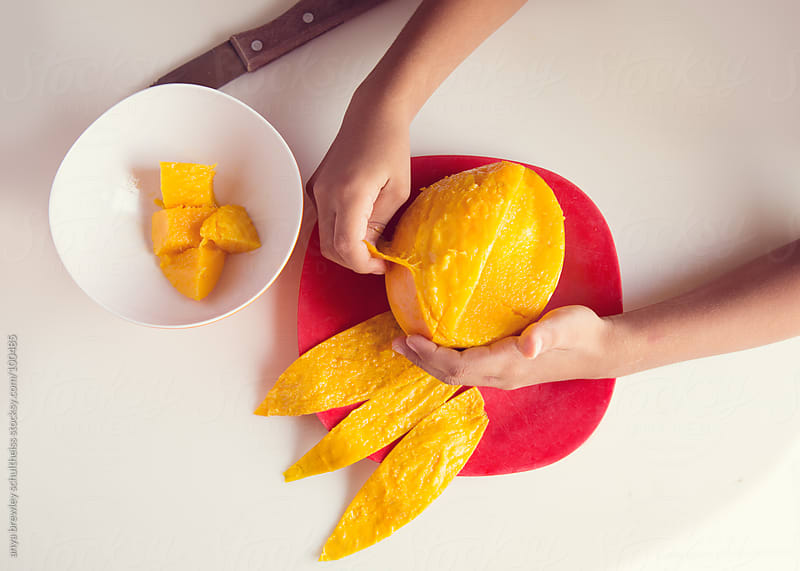 Image of a pair of hands peeling a ripe mango by anya brewley schultheiss for Stocksy United