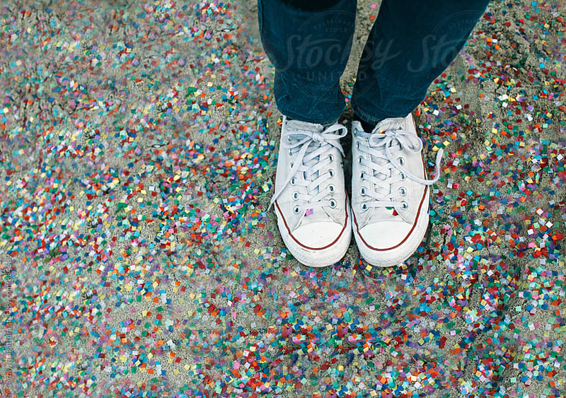 Sneakers in confetti covered sand by Carolyn Lagattuta for Stocksy United