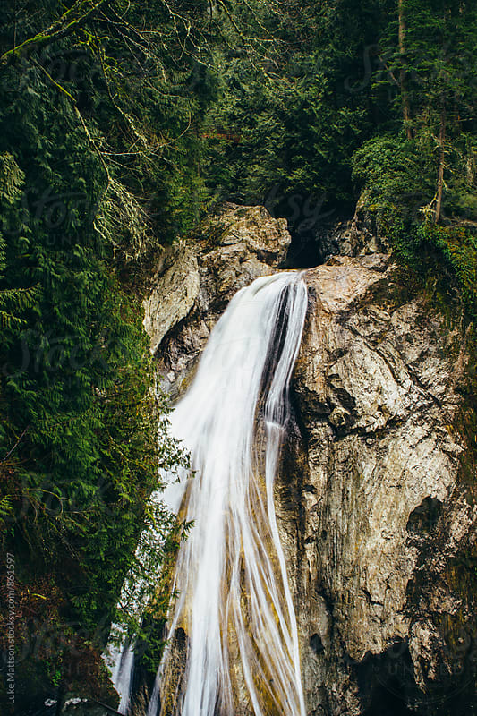 Evergreen Forest Waterfall Running Down Rock Ledge by Luke Mattson for Stocksy United